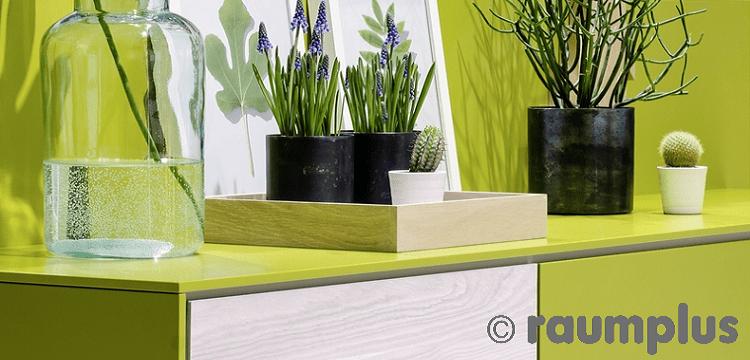 Detailansicht einer Kommode in knalligen Grün und weißer Holzoptik.